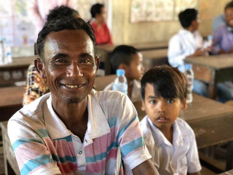 Un padre e un bambino cambogiano aiutati