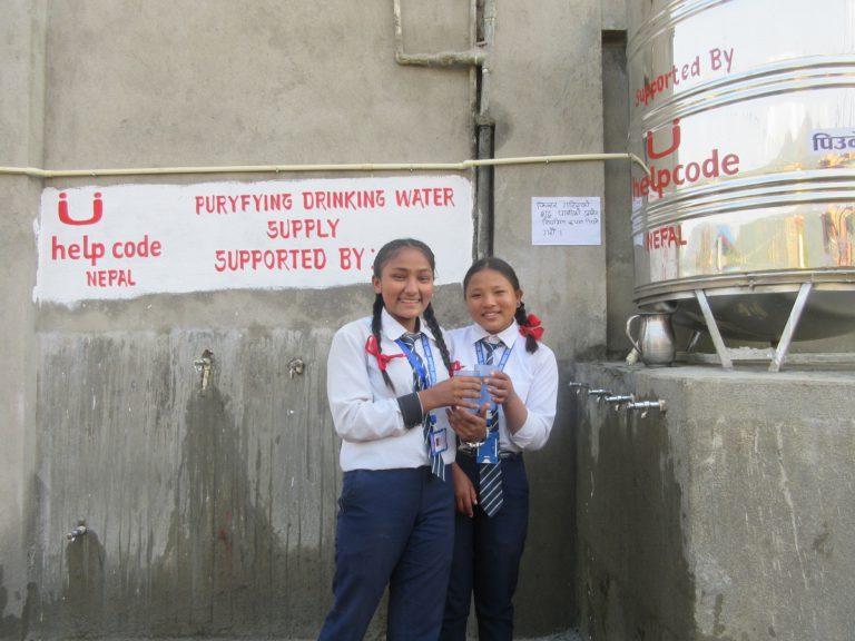 Rebika, una ragazza nepalese, insieme a una sua amica mentre bevono acqua pulita
